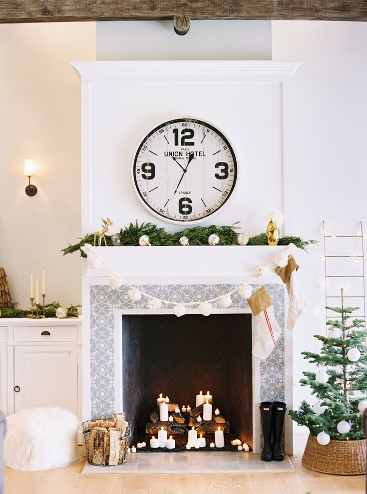 oversized clock above fireplace, candles on top of wood logs, christmas tree in a basket and wood beams #decor