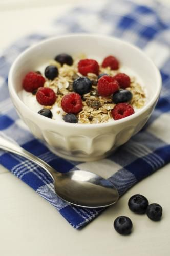healthy tasty breakfast or snack-oatmeal or muesli topped with yoghurt and fresh berries