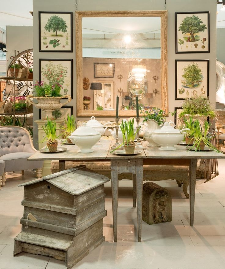 Antique beehive at the front of this stand, wonderful botanical prints on the walls and elegant metal planters and urns.