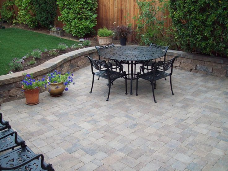 this charming back patio features paver stones container plants a wrought iron seating area and a low retaining wall