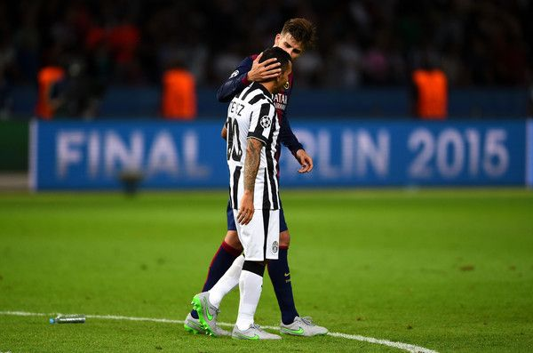 Gerard Pique of Barcelona consoles Carlos Tevez of Juventus after the UEFA Champions League Final between Juventus and FC Barcelona at Olympiastadion on June 6, 2015 in Berlin, Germany.