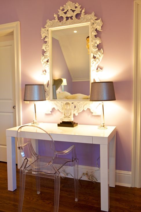 Lilac walls paint color, white Rococo mirror, Kartell Ghost Chair, West Elm Parsons Desk with Drawers in Glossy White, glass lamps with silver metallic shades and Buddha.