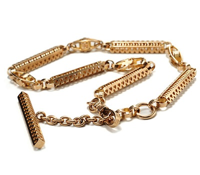 Albert Chain - Circa 1900.  A watch or fob chain named in memory of Prince Albert, consort to Queen Victorian. The Prince wore such chains as an accessory with his morning attire.  Crafted of 9k rose gold, ornate extended pierced bars accented with a saw tooth pattern alternate open work oval links. At one end is a dog clip or snap gate claps, a typical closure of the period.  A T-bar fitting, similar in configuration to the extended links, is suspended at the other end.