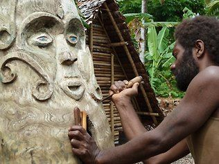 One of the local woodcarvers puts the finishing touches on the new Tam Tam in the village gathering place.