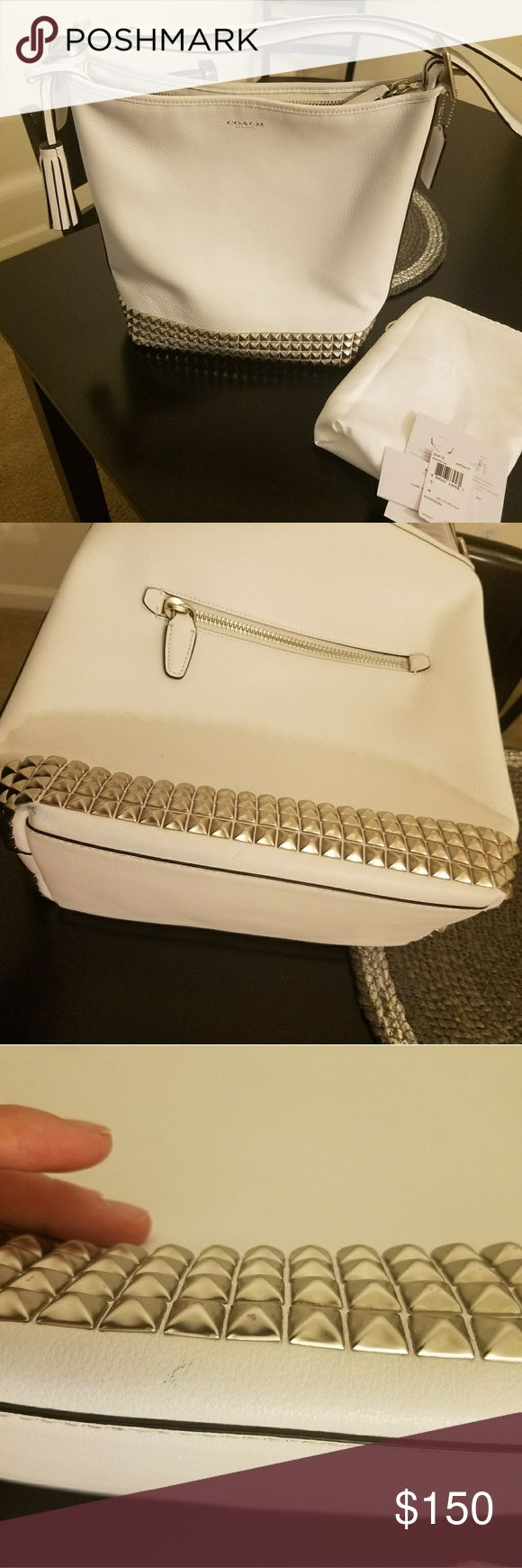 Coach Legacy White Stud Duffle White Coach legacy duffle with silver studs, all intact. Used once. See pics for minor damage on back corner of bag. Minor spots also to back of the bag also, see photos. Dust bag, original tag, care card included. beautiful bag, solid - I cannot do white. No pay pal and no trades, thanks for looking. Ask any question you have before making a reasonable offer. Coach Bags