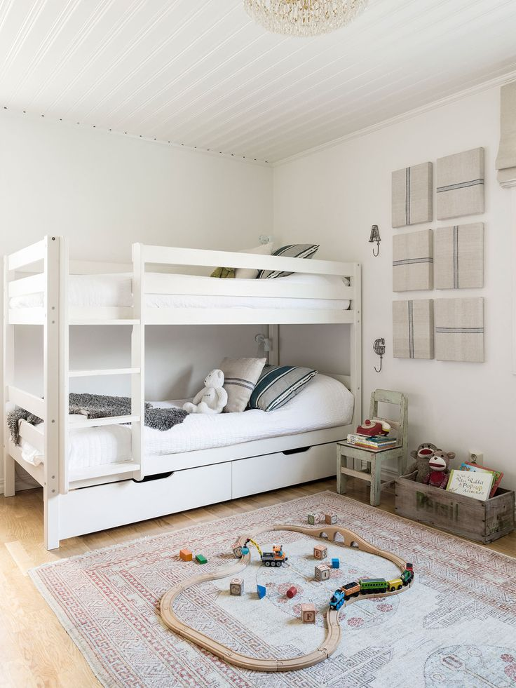 A white bunk bed is dressed with seed-sack pillows and Pottery Barn linens in the room of Wihlborg's two sons.