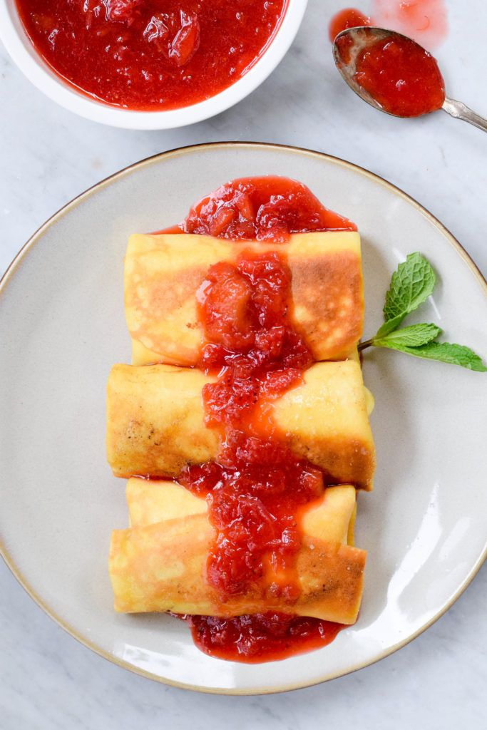 My great-grandmother's recipe for cheese blintzes with easy strawberry-rhubarb compote is the perfect brunch dish! Make ahead! Everyone loves it.