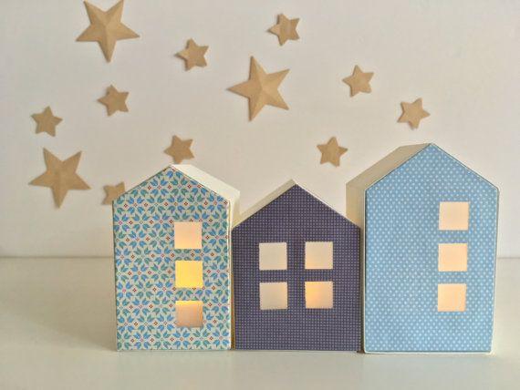 Ces 3 petites maisons photophores, confectionnées en papier, sont fait à la main, avec attention et délicatesse. De jour, comme de nuit, elles ajoutent une touche intemporelle à votre décoration. Dès la tombée de la nuit, elles s'illumineront grâce à des bougies LED (non fournies) que vous glisserez à l'intérieur.  Les maisons sont réalisées avec du papier origami dans les tons bleus, qui laisse passer une douce lumière à travers les fenêtres. Elles sont de 3 tailles différentes pour former…