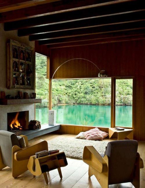 house on the edge of the water with grand windows - look at those chairs, and fireplace.