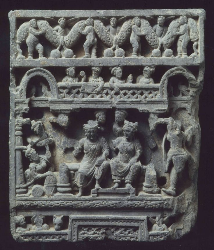 A gray schist relief of Palace Life  Gandhara, 2nd/3rd century  With Siddhartha and Yashodhara seated on the edge of the bed with musicians to the left, female attendants behind and above on a balcony flanked by arches with birds, with some figures and animals below, all capped by a frieze of putti carrying an undulating garland bearing fruit 14½ in. (36.8 cm.) high