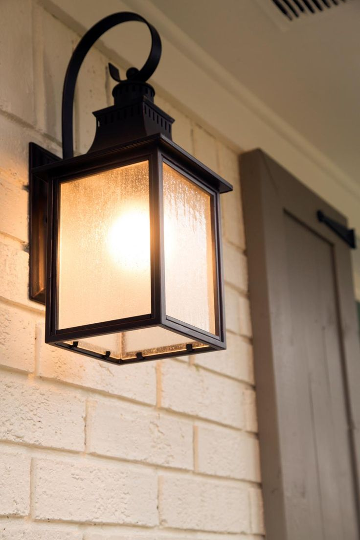 Modern metal sconces provide exterior lighting on either side of the front door.