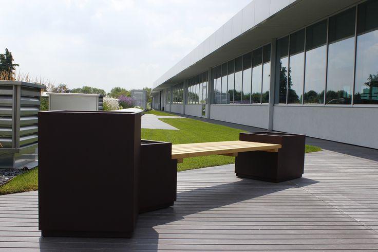 Panca in legno e vasi metallo per rilassarsi all' aperto. Sembra di essere in un parchetto siamo su un tetto di un edificio commerciale.