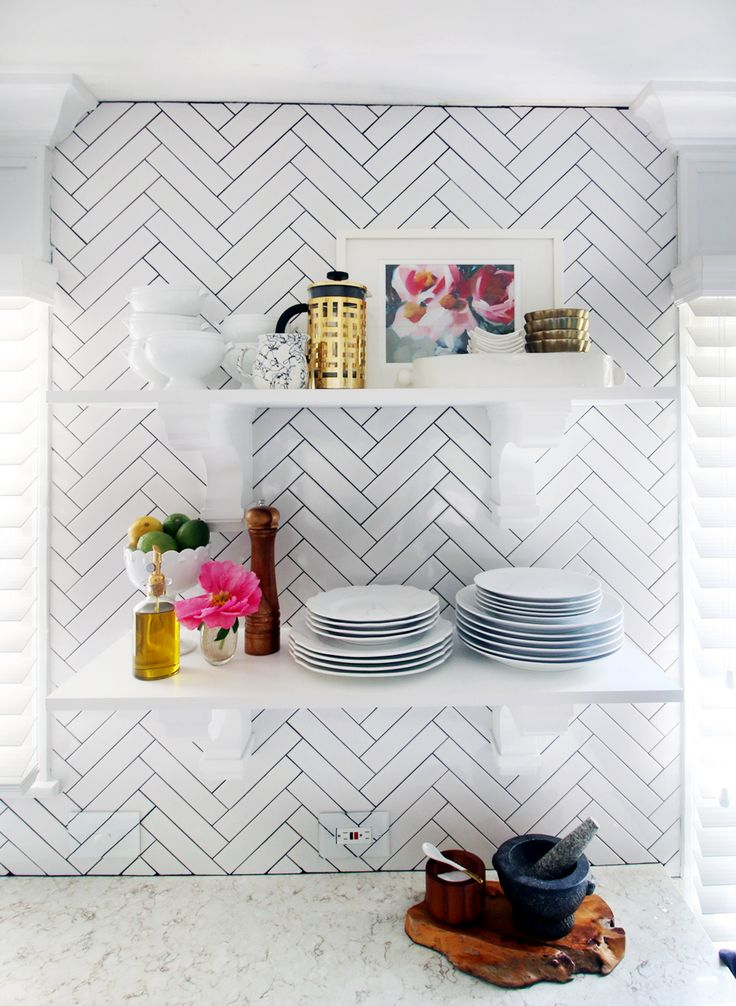 Subway tiles in herringbone pattern on kitchen wall with open shelves