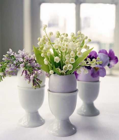 egg shell cups with spring flowers for easter table decoration