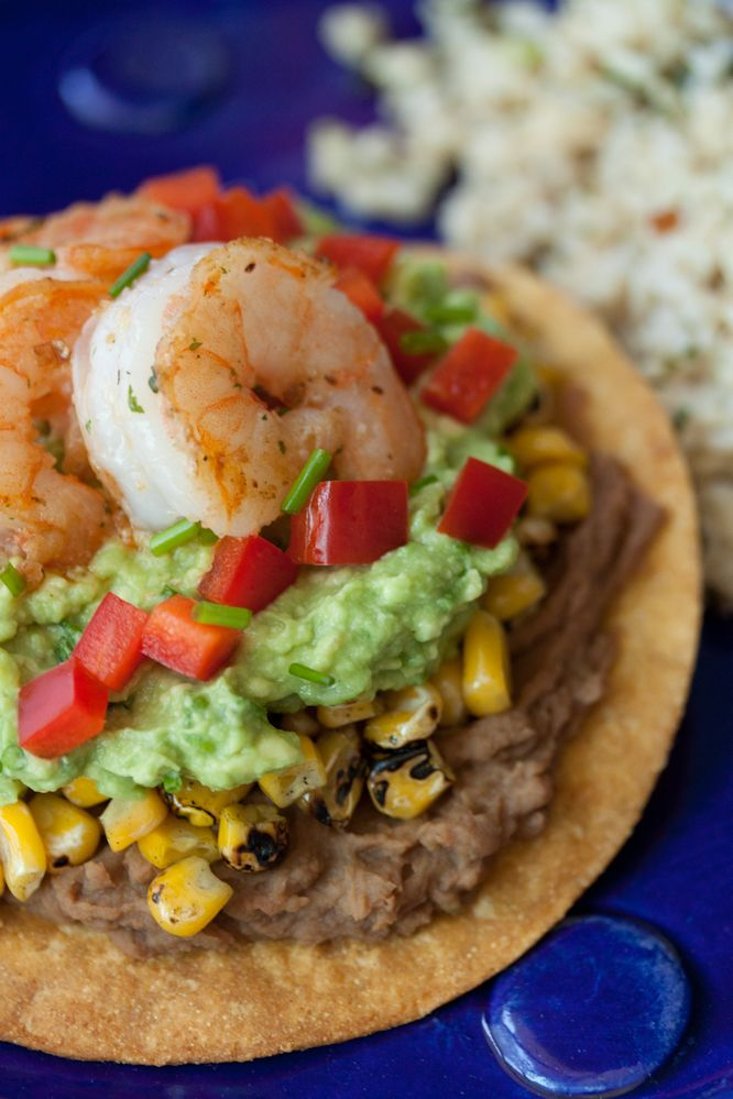 Shrimp and California Avocado Tostadas ~ small corn tortillas, grape seed oil, California Avocado, chopped chives, lime juice, refried beans, grilled corn, medium sized shrimp, red bell pepper, cayenne pepper, garlic powder, salt and pepper to taste: