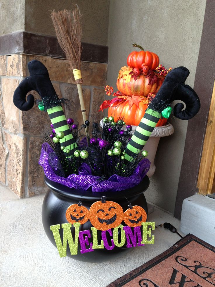 "Witch legs in a cauldron: 18"" black cauldron & cute broom (both from Harmons), purple lights, purple & black mesh, picks from Michael's, witch table legs (from celebrate express) - stuffed with a pool noodle."