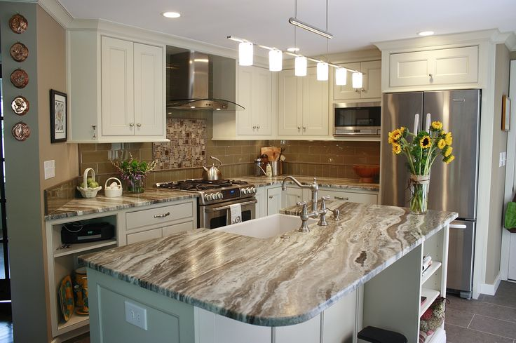 this kitchen features brown fantasy leathered quartzite countertops paired with a glass tile
