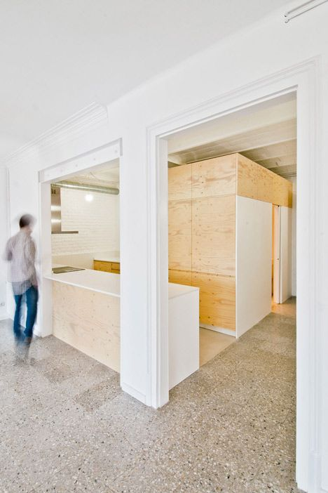 A plywood box has been inserted beneath the vaulted ceilings of an early 20th-century apartment in Barcelona to create a new bathroom and kitchen unit