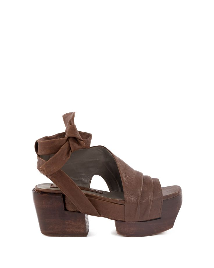 Woodden platform leather sandal with laser-cut patterned leather upper part. Closing with metal buckle. Hell height 8 cm
