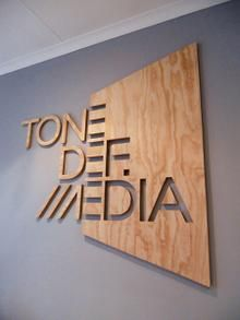 The large wooden block, smoothly textured with a nature-like tree pattern provides a stark contrast with the thin strips of the same material that are cut out to create letters.  The rotated trapezium shaped panel creates a balance between the text and empty space, and the use of overlapping the text and background creates a smooth transition of the text, from three dimensional letters to a cavity in the wooden panel, in the same font.