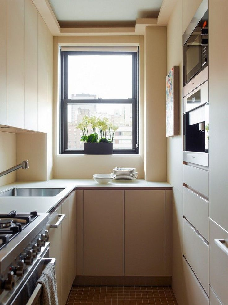 cuisine en U petit espace avec armoires blanches mates sans poignées et plaques de cuisson à gaz