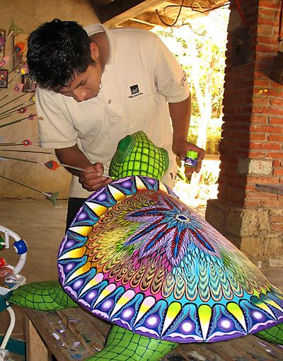 Oaxacan artist Pedro Vasques paints a giant wooden turtle carving at the Tribus Mixes compound in the village of Viguera, outside of Oaxaca.