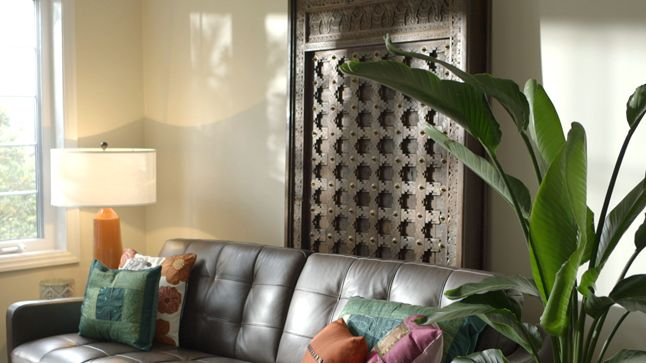 APRÈS : Pièce de résistance, une porte marocaine en bois sculpté s'érige derrière le canapé, prodiguant un cachet mille et une nuits à la pièce.