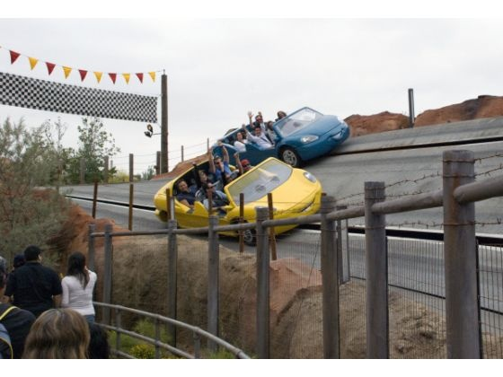 Two race cars with annual passholders as riders zip past the finish line on the Radiator Springs Racers ride that is based on the Disney/Pixar animated movie of Cars.