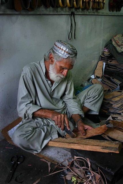 Karachi, Pakistan:     A cobbler or maker of shoes in the central market of Karachi-Pakistan. - http://pakistan.mycityportal.net