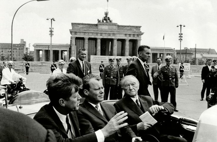Will McBride President John F. Kennedy, then Berlin Mayor Willy Brandt and German Chancellor Konrad Adenauer are pictured leaving the Brandenburg Gate in the president's open limousine on June 26, 1963. East German officials had installed drapes to block East Germans from catching a glimpse of the American president.