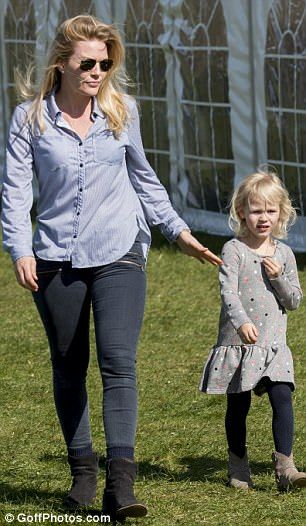 Family day out: Autumn Phillips holds out a hand to daughter Isla, four...
