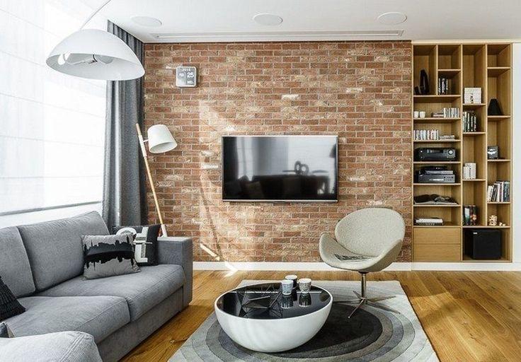 tendances déco et aménagement salon moderne - canapé gris, table basse ronde et mur de brique rouge