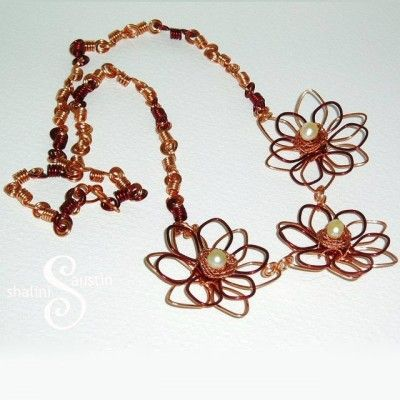 Burgundy-Copper Flower NecklaceAnother flower necklace with three flowers in the new style of flower in two colours. This one is made of pure copper and burgundy coloured copper wire.The flowers are hand crafted and the the coils in the chain are also individually handmade.
