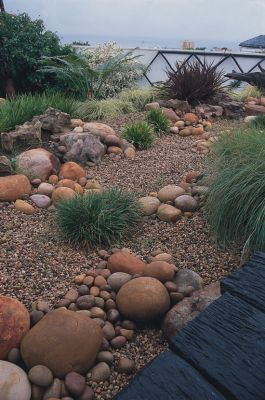 Combine a dry river bed and walk way down the side of a house to move water away from the foundation and out to front and back yards.