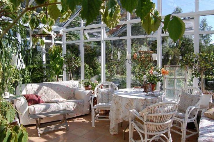 serre en verre avec mobilier à motifs floraux et plantes vertes