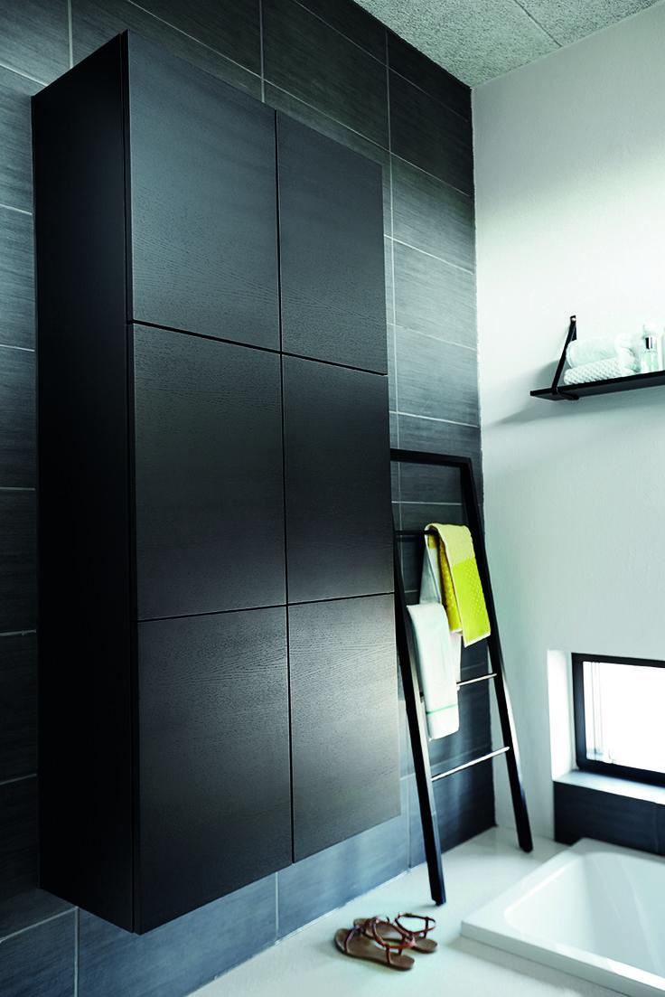 Det væghængte skab i sortbejdset egetræ giver masser af plads til fx håndklæder.