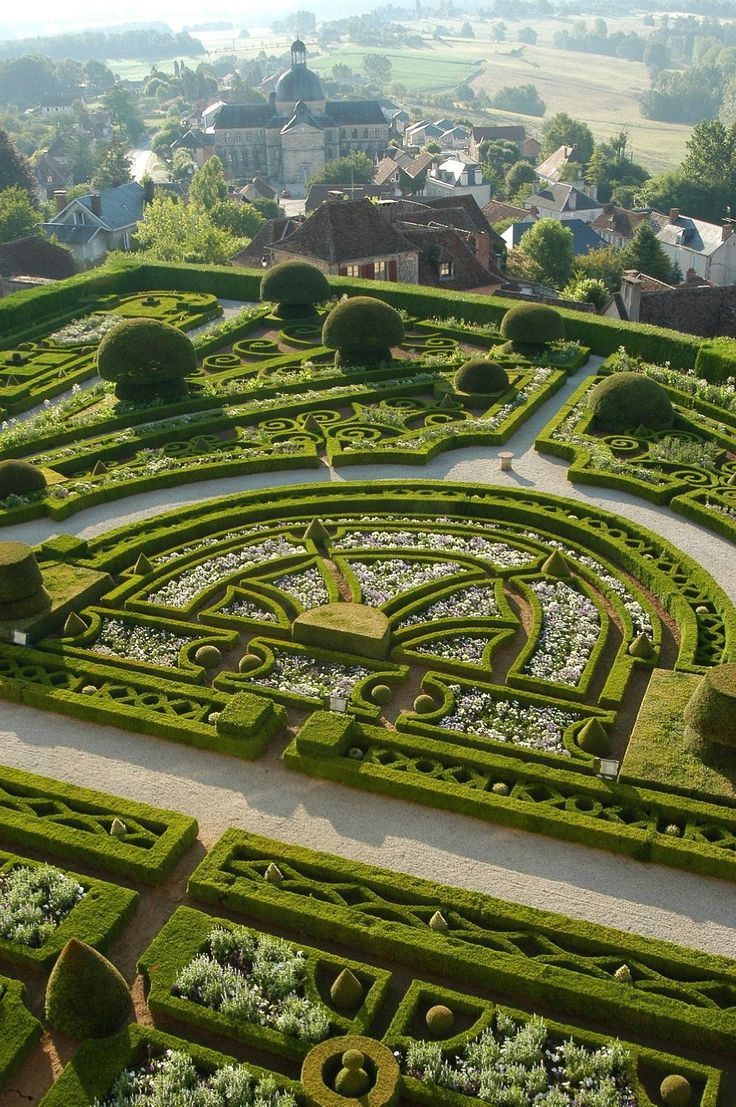 The Château de Hautefort is equally well known for, and visited for, its meticulous 'French style' gardens and the carefully landscaped parkland that surrounds it - Topiary Garden at Château de HAUTEFORT, in Hautefort, Dordogne, France