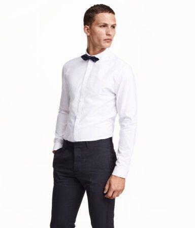 コットン織物素材の長袖シャツ。細めのターンダウンカラー。スリムフィット。襟下に付いたボタンで留めるタイプのボウタイ付き。ボウタイの幅 12cm。