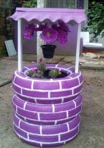Wow - this is made from recycled and painted tires! Just stack them, drill some holes, and nail a roof on. Love those hanging flowers!
