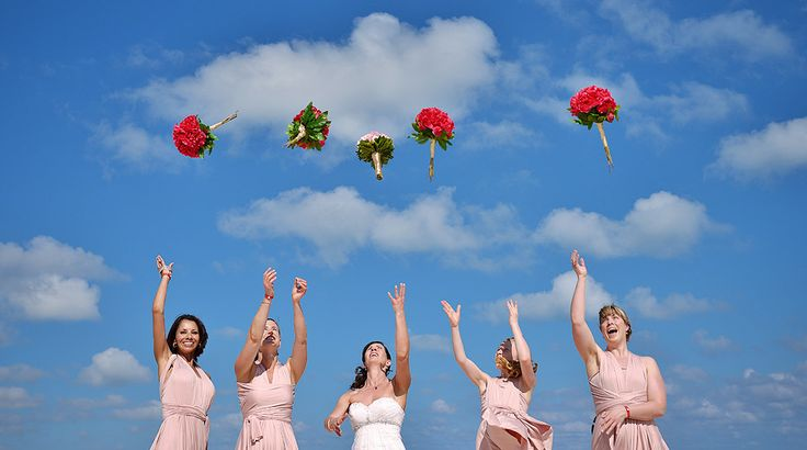 The bride and bridesmaids practice for the bouquet toss in this bridal party portrait| Palace Resorts Weddings ®