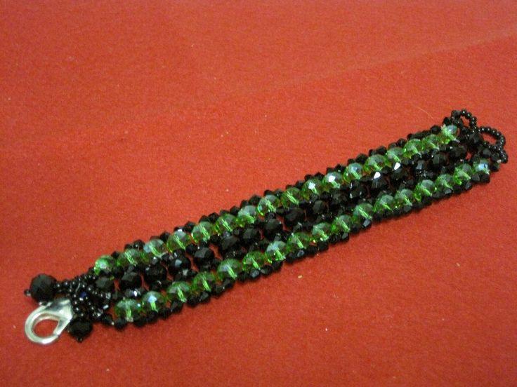 Bracciale con perle mezzo cristallo di colore verde bottiglia trasparente e di colore nero con finizioni di conteria nera. Chiusura a moschettone argentato.