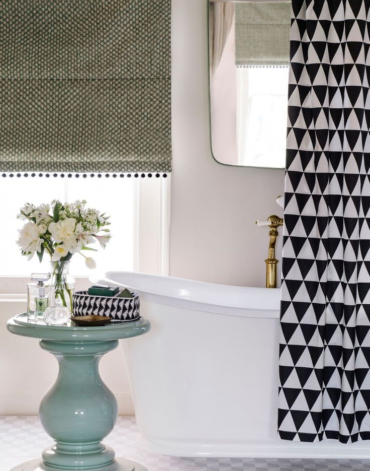 This bathroom is bang on trend thanks to the monochrome geometric theme and the mint green side table