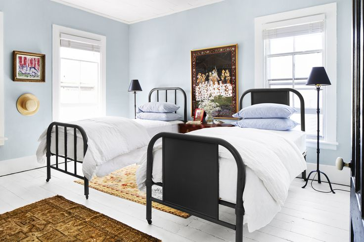 country farmhouse guest bedroom w/ metal beds, small floor lamps instead of table lamps on shared nightstand, oriental carpet on painted wood floor