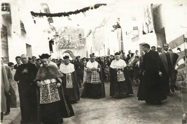 En el Homenaje a Santiago Guallar. Muniesa (1928) (Foto de Esperanza Lomba) En la calle la Fuente, al fondo la ermita de la V. de la Aliaga. (Vestimenta del clero?)