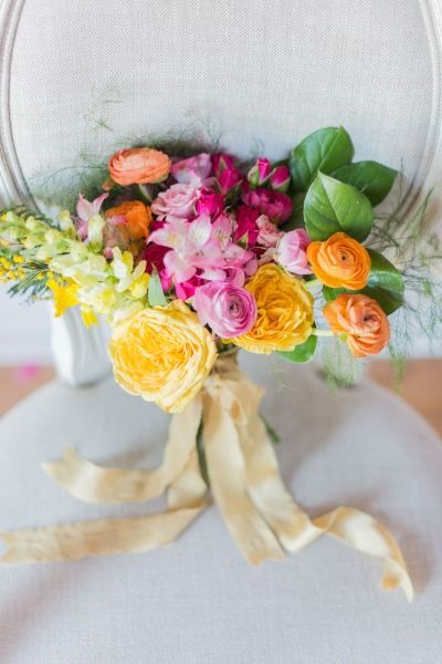 Bright colored wedding bouquet - pink, yellow + orange bouquet with roses, ranunculuses, alstroemeria, garden roses, lupines and acacia ribbons {Laura Kelly Photography}