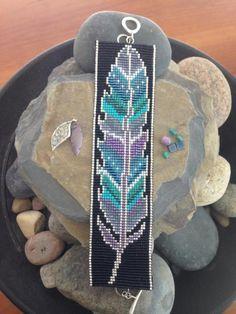 Ce bracelet de perles plume peint est le troisième d'une série. Ce un comporte delica des perles dans les tons de bleu sombre, gris, turquoise et pourpre en sourdine, mis en valeur avec du blanc dans un fini perle. La bordure et la bordure sont rendus dans les perles en argent sterling. Les anneaux de bout sont en argent sterling. Il s'attache avec fermoir en argent massif martelé. Longueur : 7,5 pouces LARGEUR : 1,5 pouces