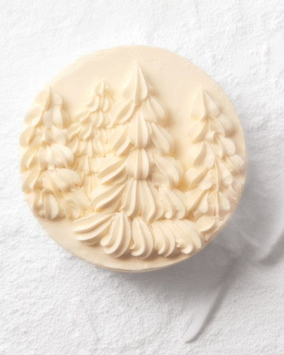 This delicate, snowy cake has coconut milk and coconut oil in the batter and shredded coconut in the vanilla buttercream icing. More buttercream covers the cake and is piped with a star tip into a fanciful forest.