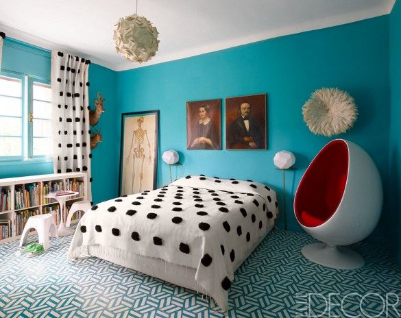 Modern bedroom with teal walls and tiled floors, egg chair, and polka dot bedding