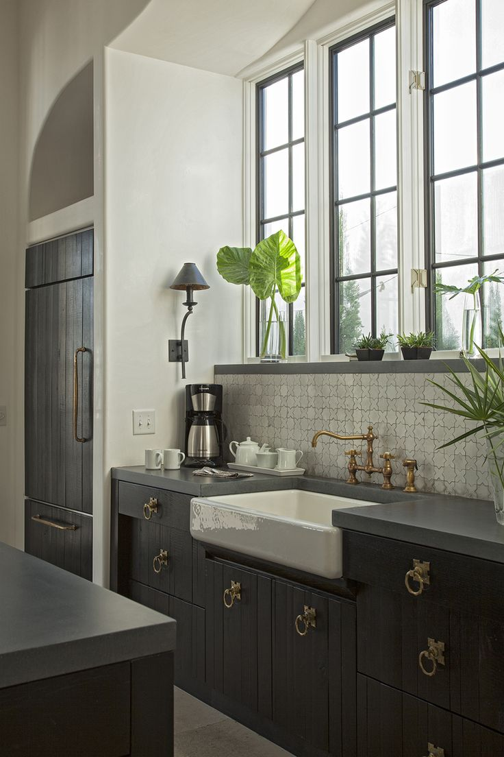 Kitchen with Moroccan tile backsplash, black cabinetry, and brass hardware. Beautiful!