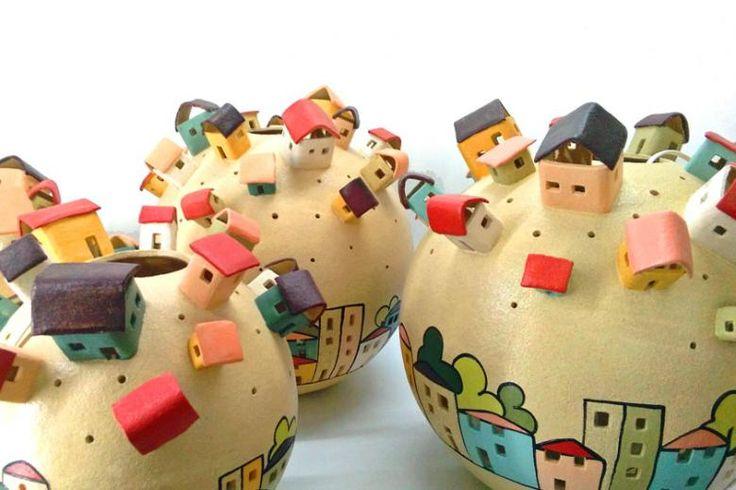 Un'altra magnifica lampada della collezione Urbe di Carla Dias. La lampada utilizza sempre lo stile tipico questa collezione che ricorda l'infanzia dell'artigiano, con l'aggiunta di casette in rilievo dai colori molto vivaci. Un design allegro, colorato e moderno che si adatta a vari ambienti.